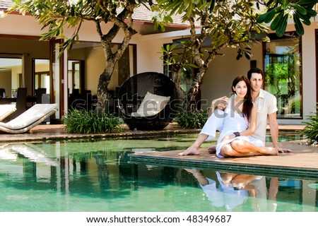 An attractive couple relaxing by the pool outdoors - stock photo