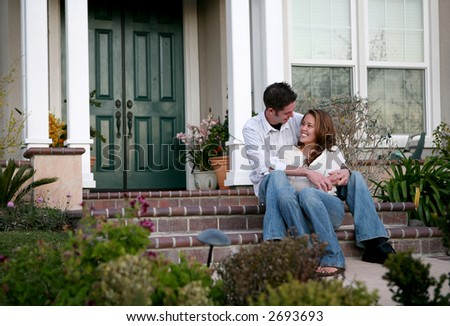 An attractive couple relaxing in front of their home - stock photo