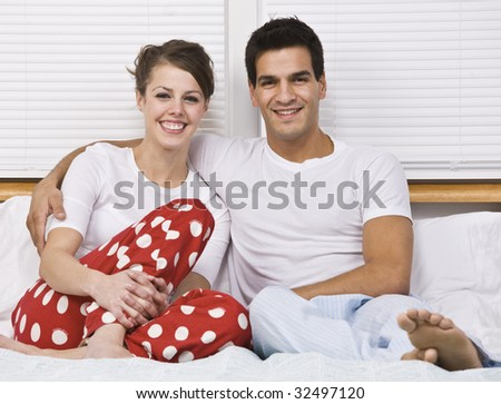 An attractive couple smiling and sitting in bed together.  Horizontally framed shot. - stock photo