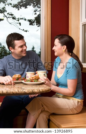 An attractive couple talking over breakfast by a large window, with a picturesque background, at home.  Vertically framed shot. - stock photo