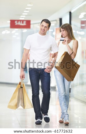 An attractive couple with a credit card at the store - stock photo