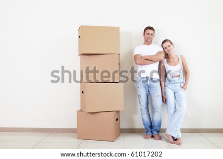 An attractive couple with boxes in new home - stock photo