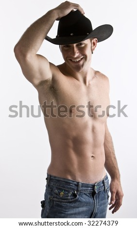 An attractive cowboy with his shirt off in studio - stock photo