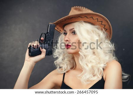 An attractive cowgirl.girl in a cowboy hat with a gun - stock photo