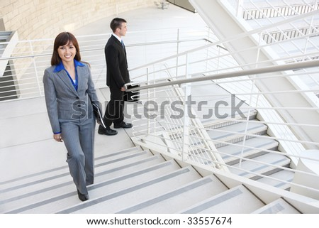 An attractive, diverse business man and woman  on stairs at office building - stock photo