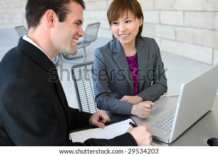 An attractive, diverse business team at the office building with laptop computer