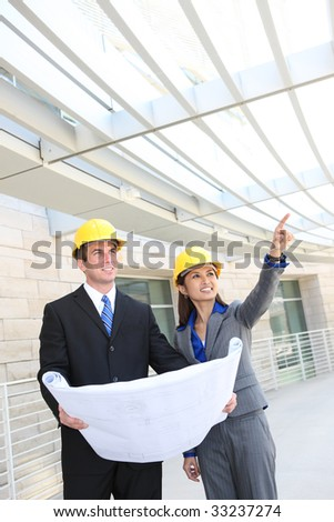 An attractive, diverse man and woman construction team at building site - stock photo