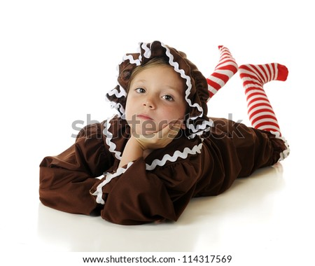 """An attractive elementary """"gingerbread girl"""" laying on her belly, clicking her candy-striped heals together.  On a white background. - stock photo"""