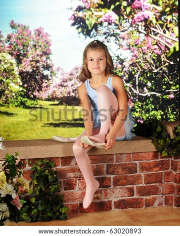 An attractive elementary girl in her ballet dress, putting on her slippers on a garden wall. - stock photo