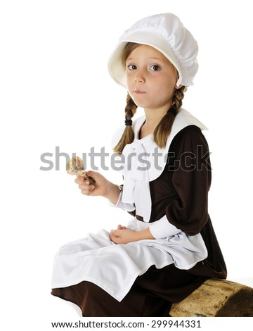 An attractive elementary Pilgrim girl sitting on a log with a mouth full of roast chicken.  On a white background. - stock photo