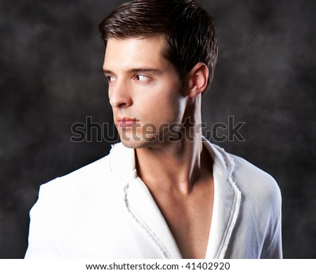 An attractive fashion man in a white environment - stock photo
