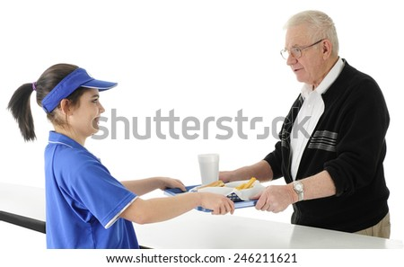 An attractive fast food employee serving a tray of fast food to a senior adult man.  On a white background. - stock photo
