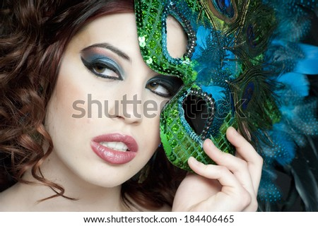 An attractive female headshot with a green mask.