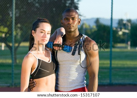 An attractive, fit couple is standing together on a tennis court.  They are holding their workout gear and looking at the camera.  Horizontally framed shot.