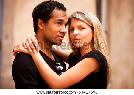An attractive french couple in an outdoor urban setting - stock photo