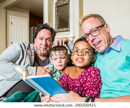 An attractive gay couple reads to their children in living room - stock photo