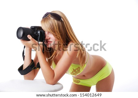 An attractive girl is shooting with DSLR. She is wearing yellow bikini and sunglasses. The blonde is setting her elbows on the table and bending her sexy body forward.