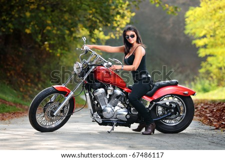 An attractive girl on a motorbike posing outside - stock photo