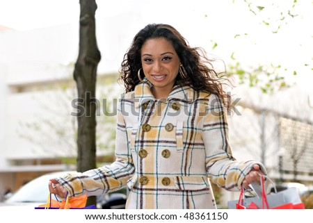 An attractive girl out shopping in the city with lots of bags. - stock photo