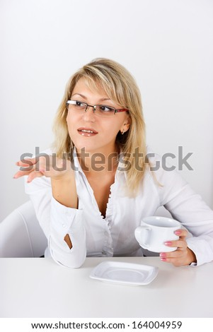 An attractive girl with a cup in the office gesticulates - stock photo