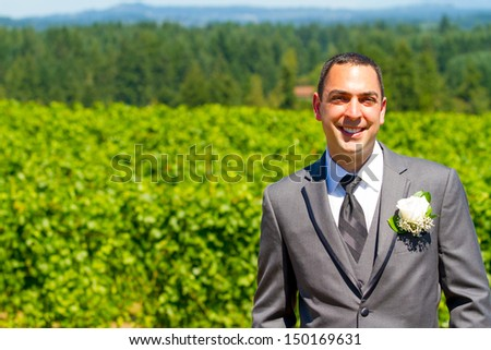 An attractive groom poses for a portrait on his happy wedding day outside at a winery vineyard in Oregon during the summer. - stock photo