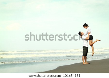 An attractive happy couple having fun on the beach - stock photo