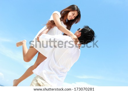 An attractive happy couple having fun together on the beach - stock photo