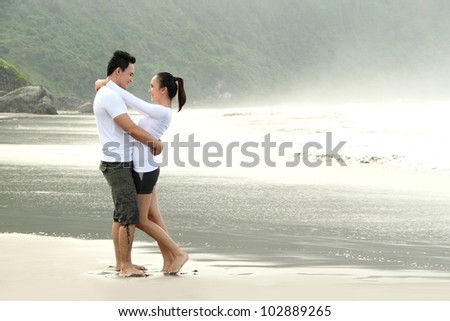 An attractive happy couple hugging on the beach - stock photo