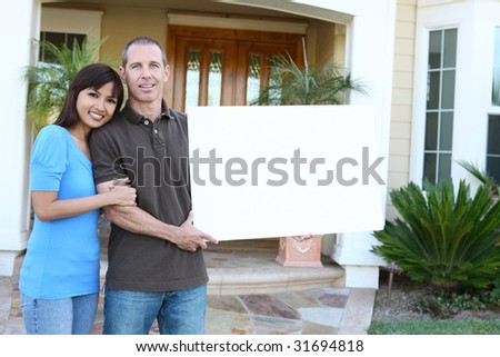 An attractive happy couple in front of their home holding a sign - stock photo
