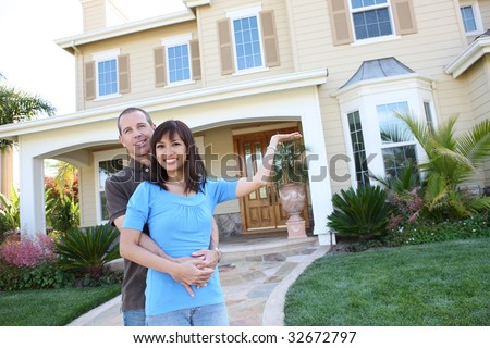 An attractive happy diverse couple in front of their home in love - stock photo