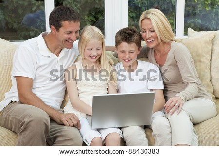 An attractive happy, family of mother, father, son and daughter sitting on a sofa at home having fun using a laptop or computer - stock photo