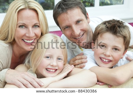 An attractive happy, family of mother, father, son and daughter sitting on a sofa at home having fun - stock photo