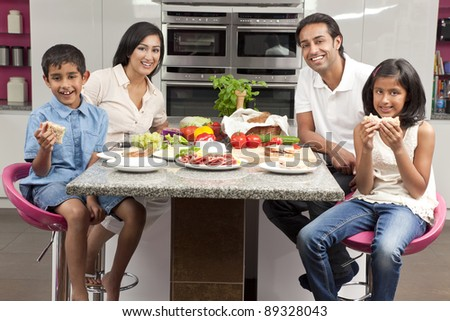An attractive happy, smiling Asian Indian family of mother, father, son and daughter eating healthy food & salad in the kitchen at home - stock photo