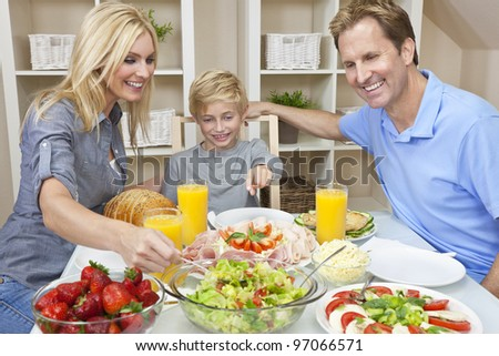 An attractive happy, smiling family of mother, father and son eating salad and healthy food at a dining table - stock photo