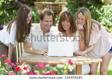 An attractive happy, smiling family of mother, father and two daughters sitting using a laptop computer outside in the garden in warm summer sunshine - stock photo