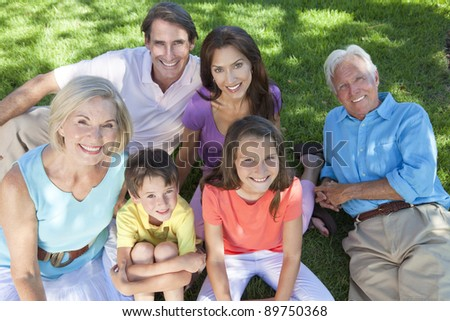 An attractive happy, smiling family of mother, father, grandparents, son and daughter sitting on the grass outside or in a garden together.