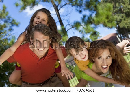 An attractive happy, smiling family of mother, father, son and daughter having fun outside in a park in warm summer sunshine