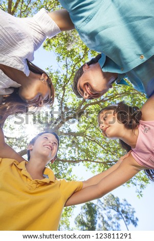 An attractive happy, smiling family of mother, father, son and daughter hugging in a huddle together outside in a park enjoying warm summer sunshine - stock photo