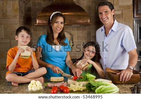 An attractive happy, smiling family of mother, father, son and daughter making healthy sandwiches with ham, cheese and fresh salad in a modern kitchen - stock photo