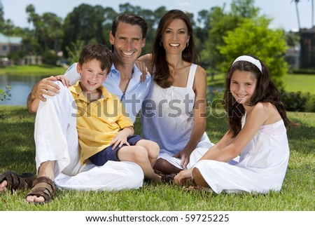 An attractive happy, smiling family of mother, father, son and daughter sitting on grass outside in warm summer sunshine - stock photo