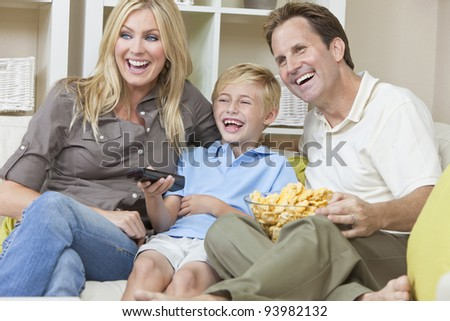 An attractive happy, young family of mother, father and son sitting on a sofa at home llaughing watching television and eating a snack - stock photo