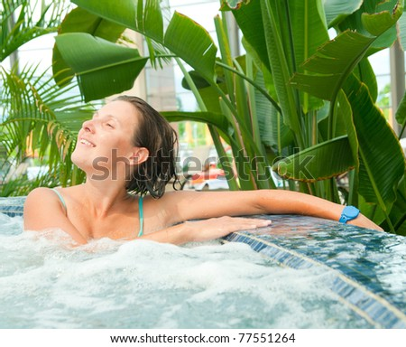 An attractive happy young woman spends relaxing in the Jacuzzi - stock photo