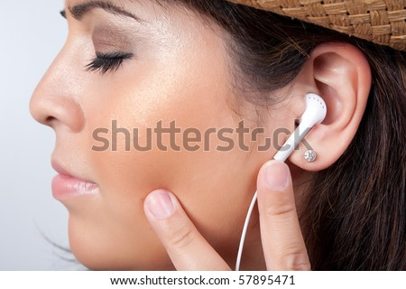 An attractive Hispanic woman listening to and getting into the music playing through her stereo ear bud headphones.