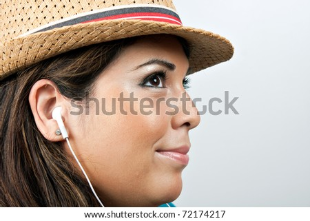 An attractive Hispanic woman listening to music playing through her stereo earbud headphones. - stock photo