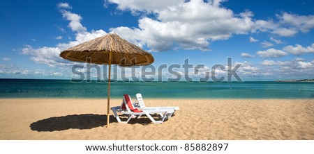 An attractive image of two chairs and umbrella on the beach