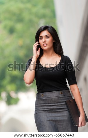 An attractive Indian businesswoman outside - stock photo