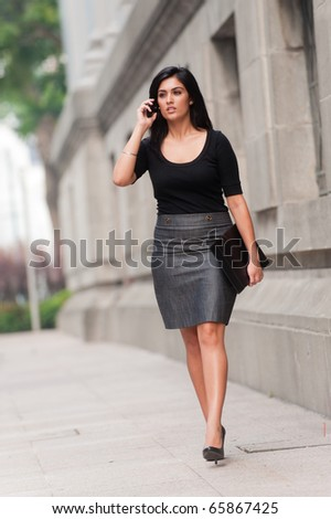 An attractive Indian businesswoman outside with mobile phone