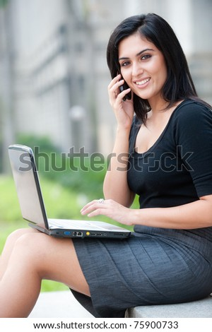 An attractive Indian businesswoman sitting outside with laptop and phone - stock photo