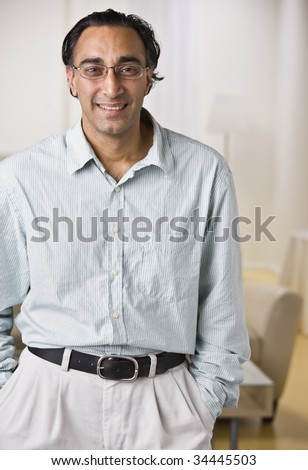 An attractive Indian man posing.  He is dressed in business attire and is smiling at the camera.  Vertically framed shot. - stock photo
