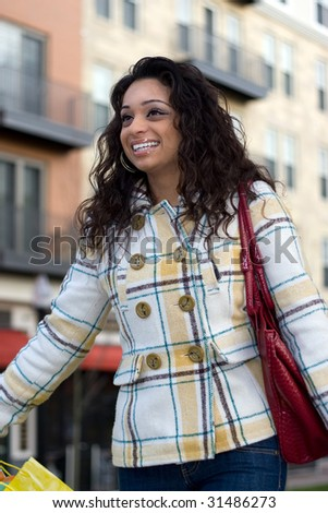 An attractive Indian woman out shopping in the city. - stock photo